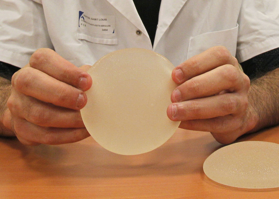 Photo - FOR STORY BRITAIN COSMETIC SURGERY - FILE - In this Wednesday, Dec. 21, 2011, file photo Dr. Maurice Mimoun, a plastic surgeon at the St Louis hospital in Paris holds a silicone gel breast implant made by French company Poly Implant Prothese, or PIP, that he removed from a patient because of concerns that they are unsafe. An independent expert group released a report Wednesday April 24, 2013, which slammed Britain's cosmetic surgery industry for not protecting patients adequately and is calling for stricter controls in the aftermath of a breast implant scandal in Europe last year that left tens of thousands of women with cheap silicone implants prone to ruptures. The expert group, commissioned by the U.K. Department of Health, also called for the creation of a registry of implants and other medical devices. (AP Photo/Michel Euler, File)