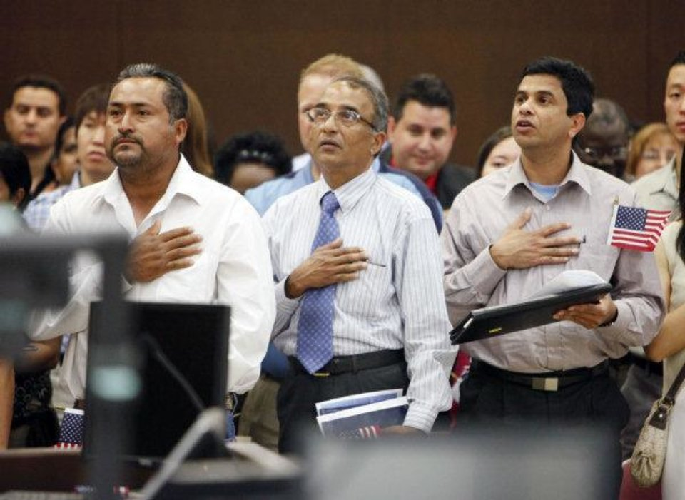 Photo - Former Mexican citizen Ernesto Rosas (left) and former Indian citizens Simon Mascarenhas and George Varghese recite the Pledge of Allegiance during a naturalization ceremony June 24 at the federal courthouse in Oklahoma City.  PAUL HELLSTERN - THE OKLAHOMAN