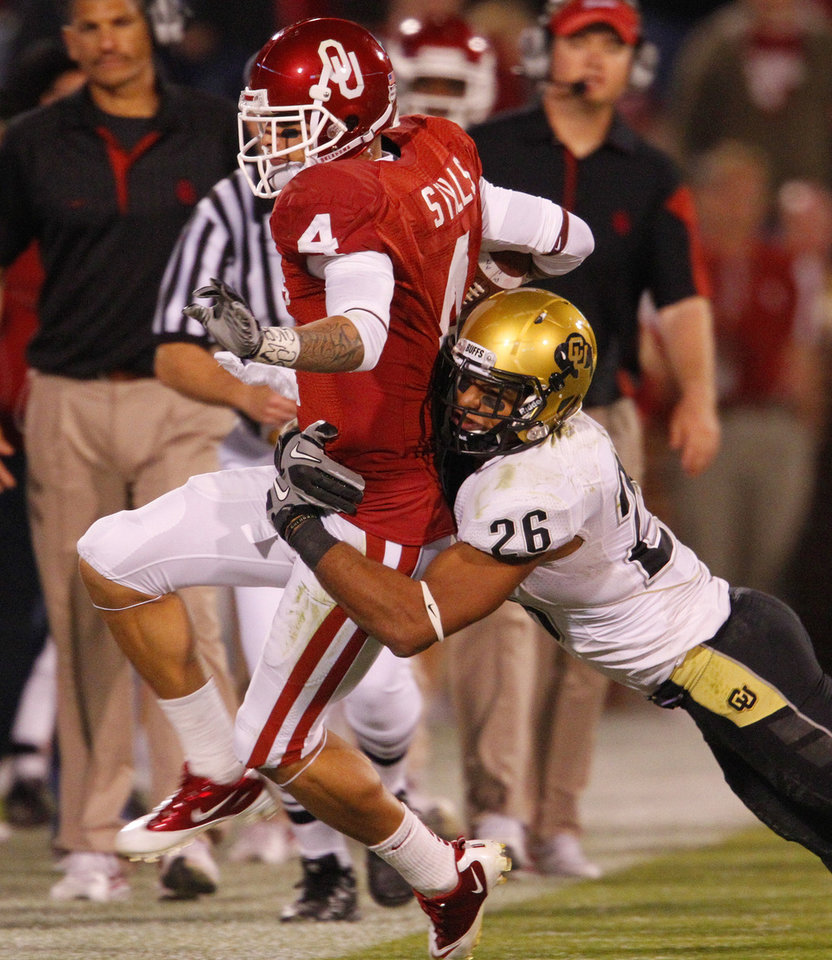 Photo - Kenny Stills (4) is tackled by Tony Jones (26) during the first half of the college football game between the University of Oklahoma (OU) Sooners and the University of Colorado Buffaloes at Gaylord Family-Oklahoma Memorial Stadium in Norman, Okla., Saturday, October 30, 2010.  Photo by Steve Sisney, The Oklahoman