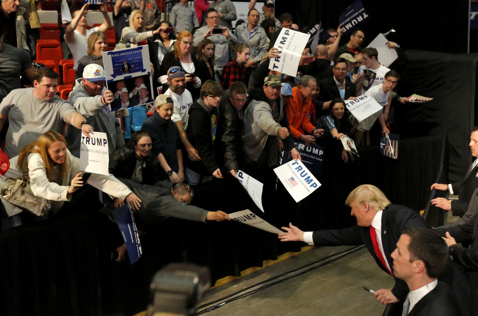 Photo - Republican presidential candidate Donald Trump reaches for a sign to autograph after a rally at the Cox Convention Center in Oklahoma City, Friday, Feb. 26, 2016. Photo by Bryan Terry, The Oklahoman