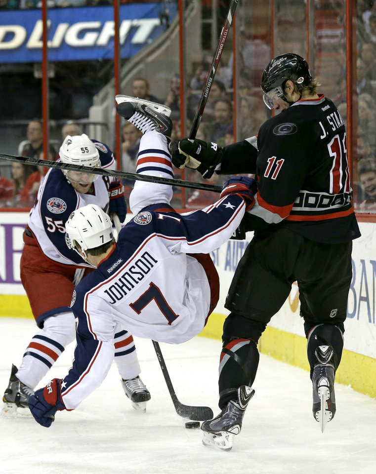 Photo - Columbus Blue Jackets' Jack Johnson (7) falls as Carolina Hurricanes ' Jordan Staal (11) and Blue Jackets' Mark Letestu (55) chase the puck during the second period of an NHL hockey game in Raleigh, N.C., Monday, Jan. 27, 2014. (AP Photo/Gerry Broome)