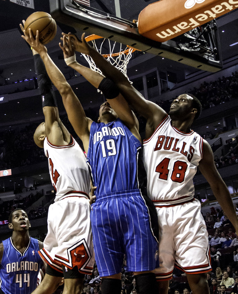 Photo -   Chicago Bulls' Taj Gibson (22) and Nazr Mohammed (48) put defensive pressure on Orlando Magic's Gustavo Avon during an NBA basketball game in Chicago on Tuesday, Nov. 6, 2012.(AP Photo/Charles Cherney)