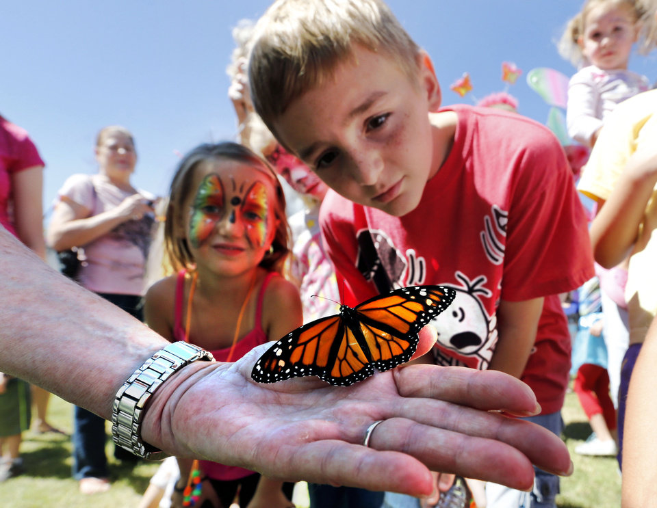 Photo - Linda Schemmer holds a monarch butterfly in the palm of her hand while children examine it at the Monarch Migration and Butterfly Festival Saturday in Cole. PHOTO BY STEVE SISNEY, THE OKLAHOMAN  STEVE SISNEY