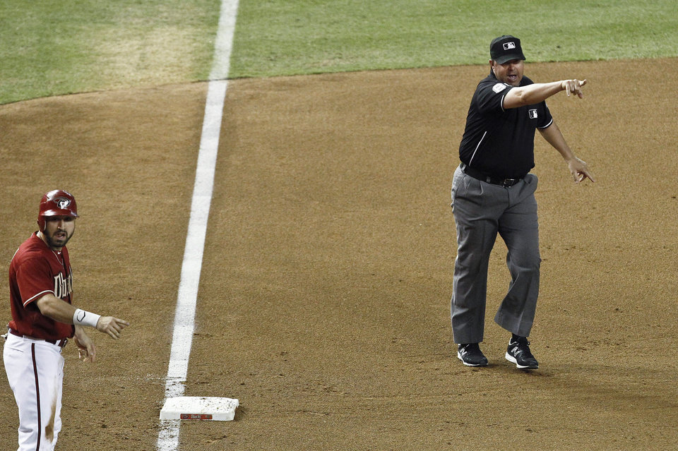 Photo -   Third base umpire Doug Eddings, right, signals a balk on San Diego Padres' Edinson Volquez as Arizona Diamondbacks' Adam Eaton, left, points at the pitcher as well during the fifth inning of a baseball game Wednesday, Sept. 19, 2012, in Phoenix. Eaton scored on the balk. (AP Photo/Ross D. Franklin)