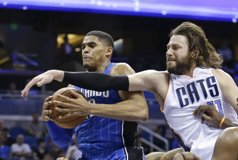 Photo - Orlando Magic's Tobias Harris, left, grabs a rebound away from  Charlotte Bobcats forward Josh McRoberts, right, during the second half of an NBA basketball game in Orlando, Fla., Friday, March 28, 2014. Orlando won in overtime, 110-105. (AP Photo/John Raoux)