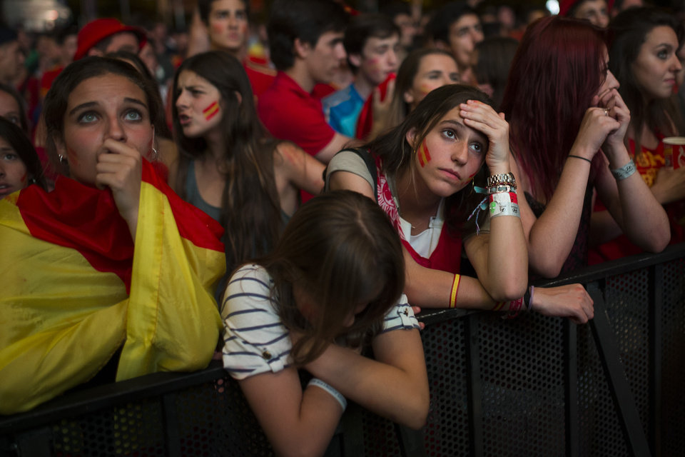Photo - Spanish soccer fans gesture as they watch on a giant display the World Cup soccer match between Spain and Chile, in Madrid, Spain, Wednesday, June 18, 2014. (AP Photo/Andres Kudacki)