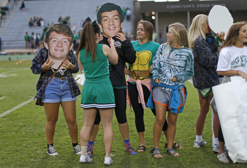 Photo - Bishop McGuinness students get ready to cheer for their team with large cutout heads of the Bishop McGuinness football players before a game against Weatherford in Oklahoma City, Friday, Sept. 20, 2013. Photo by Bryan Terry, The Oklahoman