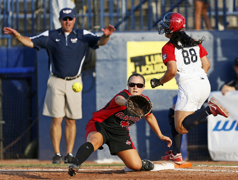 Photo - Raven Chavanne (88) of the United States makes it safely to first base before Kelsey Haberl (30) of Canada can make the catch in the second inning during a game between Team USA and Canada in the World Cup of Softball at ASA Hall of Fame Stadium in Oklahoma City, Thursday, July 11, 2013. Team USA won 7-0 in 6 innings. Photo by Nate Billings, The Oklahoman