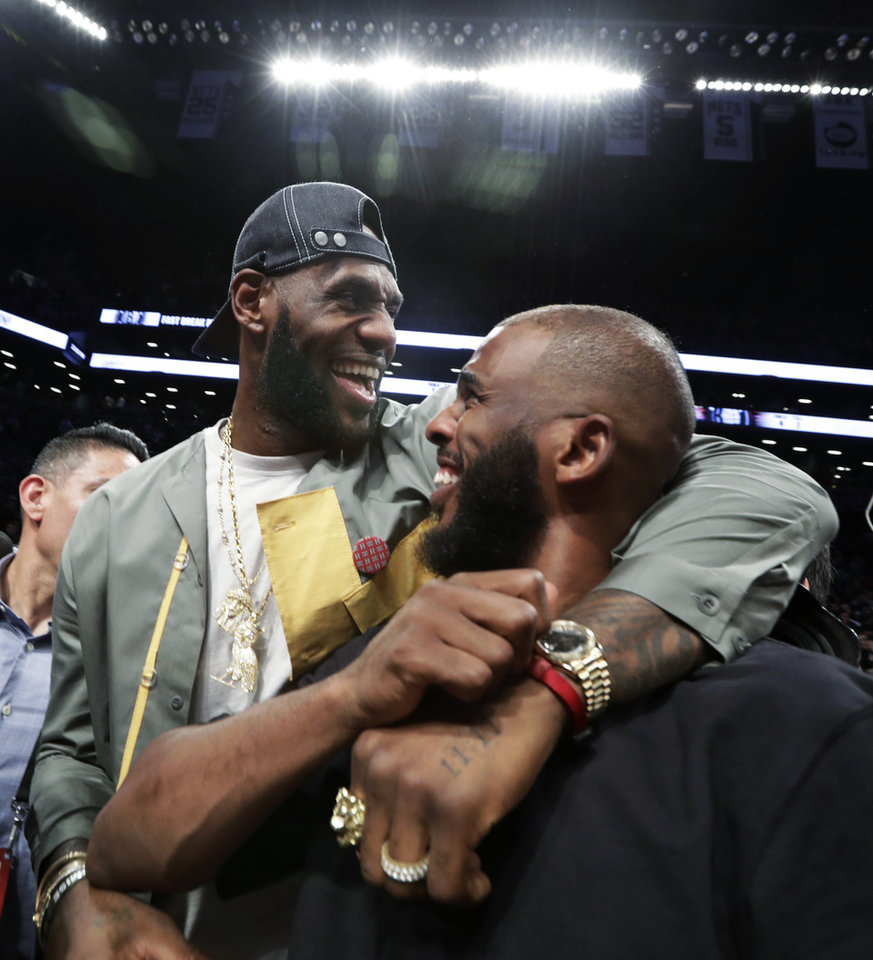 Photo - LeBron James embraces Chris Paul following an NBA basketball game between the Brooklyn Nets and the Miami Heat, Wednesday, April 10, 2019, in New York. The pair, along with Carmelo Anthony, were in New York to watch Dwyane Wade's final NBA game. (AP Photo/Kathy Willens)