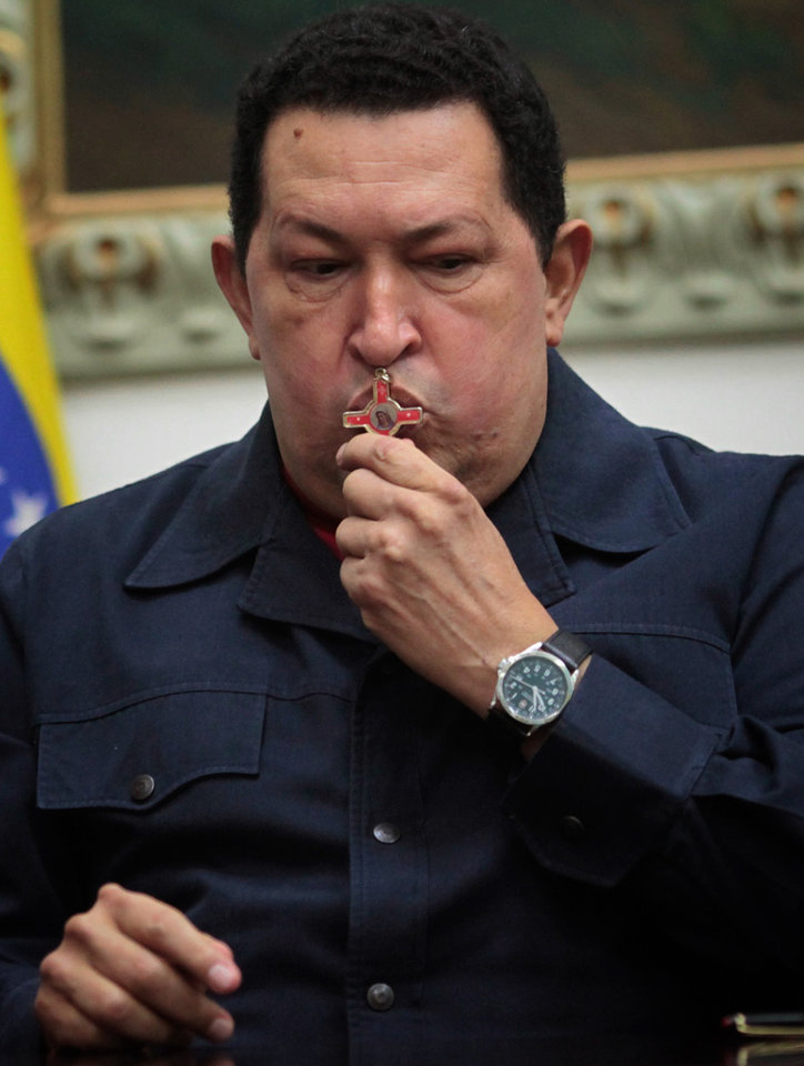 Photo - ALTERNATIVE CROP OF XFLL103,- In this photo released by Miraflores Press Office, Venezuela's President Hugo Chavez kisses a crucifix during a televised speech form his office at Miraflores Presidential palace in Caracas, Venezuela, Saturday, Dec. 8, 2012. Chavez announced Saturday night that his cancer has returned and that he will undergo another surgery in Cuba. Chavez, who won re-election on Oct. 7, also said for the first time that if his health were to worsen, his successor would be Vice President Nicolas Maduro.(AP Photo/Miraflores Press Office, Marcelo Garcia)