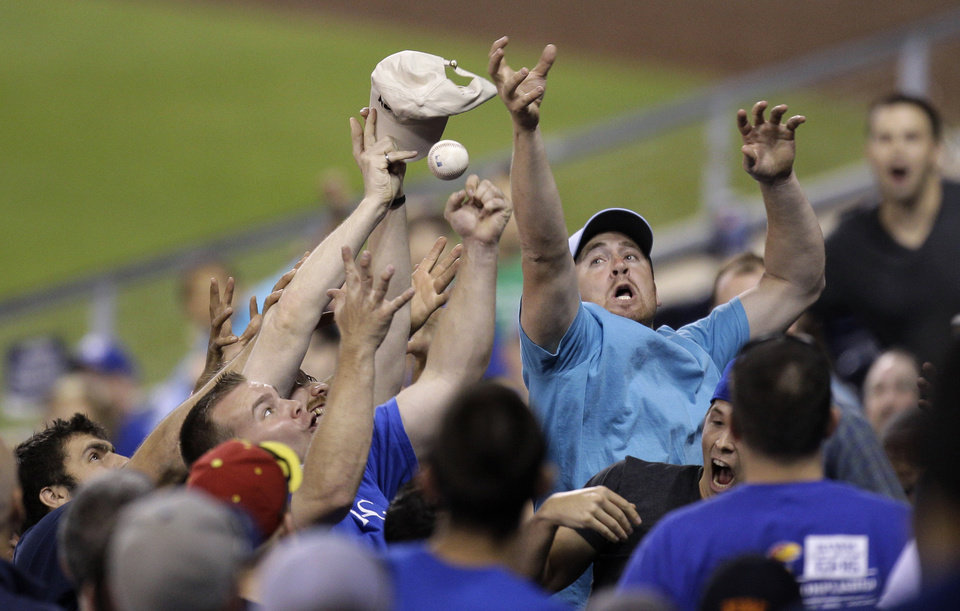 Fans try to catch a foul ball hit by Detroit Tigers' Miguel Cabrera during the ninth inning of a baseball game against the Kansas City Royals on Wednesday, April 18, 2012, in Kansas City, Mo. (AP Photo/Charlie Riedel)