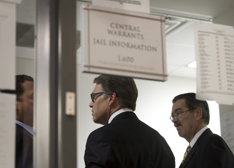 Photo - Texas Gov. Rick Perry, middle, is booked at the Blackwell-Thurman Criminal Justice Center in Austin, Texas, for two felony indictments of abuse of power on Tuesday, Aug. 19, 2014, in Austin, Texas. (AP Photo/Austin American-Statesman, Jay Janner)