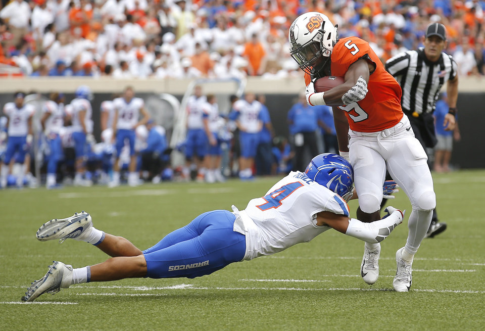 Photo - Oklahoma State's Justice Hill (5) gets by Boise State's DeAndre Pierce (4) on the way to a touchdown in the second quarter during a college football game between the Oklahoma State Cowboys (OSU) and the Boise State Broncos at Boone Pickens Stadium in Stillwater, Okla., Saturday, Sept. 15, 2018. Photo by Sarah Phipps, The Oklahoman
