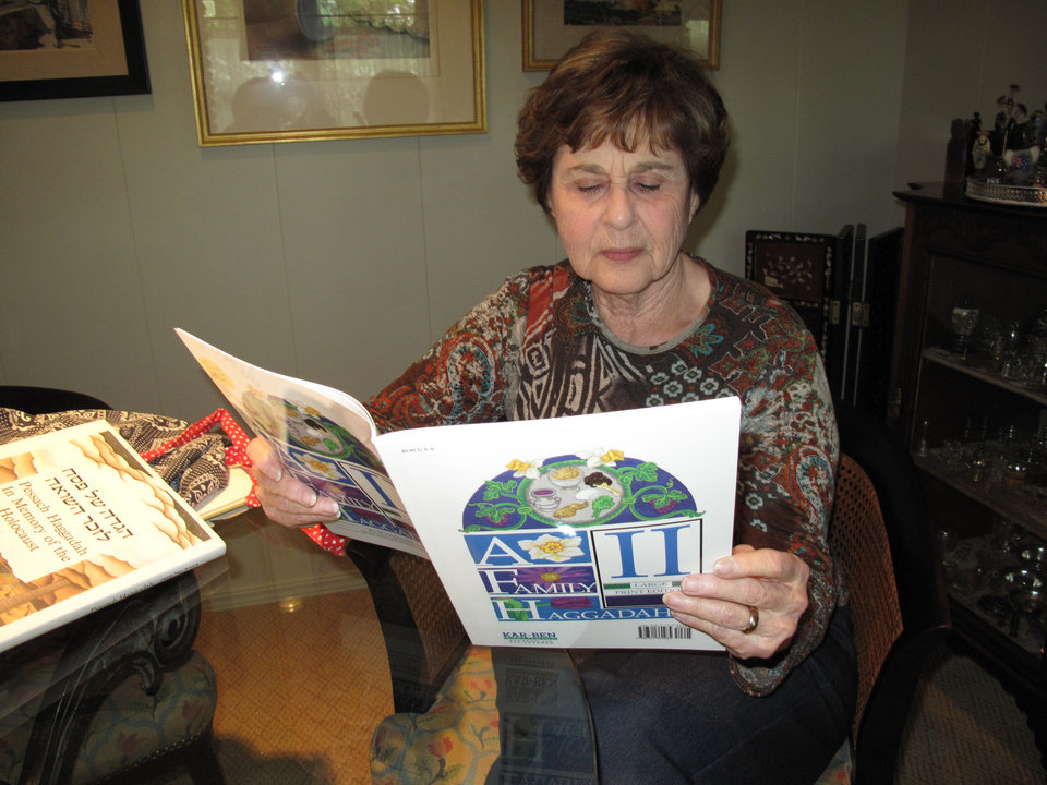 "Photo - Helene Harpman of Oklahoma City reads ""A Family Haggadah II,"" which she planned to use for a three-family Passover seder at her home. Photo by CARLA HINTON, The Oklahoman"