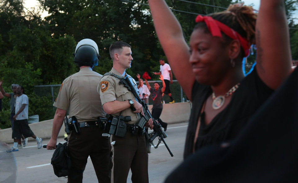 Photo - St. Louis County police officers stand back to back as they attempt to move a crowd gathered in front of the QuikTrip, Monday, Aug. 11, 2014, in Ferguson, Mo. Authorities in Ferguson used tear gas and rubber bullets to try to disperse a large crowd Monday night that had gathered at the site of a burned-out convenience store damaged a night earlier, when many businesses in the area were looted. (AP Photo/St. Louis Post-Dispatch, Robert Cohen)  EDWARDSVILLE INTELLIGENCER OUT; THE ALTON TELEGRAPH OUT