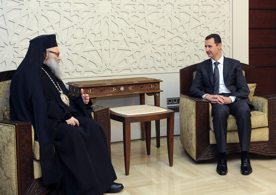 Photo - In this photo released by the Syrian official news agency SANA, Syrian President Bashar Assad, right, meets with Patriarch John Yazigi, the Eastern Orthodox Patriarch of Antioch and All the East, in Damascus, Syria, Monday, Feb. 11, 2013. Syrian rebels captured the country's largest dam on Monday after days of intense clashes, giving them control over water and electricity supplies for much of the country in a major blow to President Bashar Assad's regime. (AP Photo/SANA)