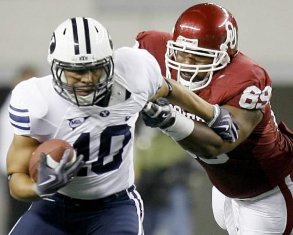 Photo - OU's Cordero Moore tries to bring down BYU's JJ Di Luigi during the college football game between the Brigham Young University Cougars ( BYU) and the University of Oklahoma Sooners (OU) at Cowboys Stadium in Arlington, Texas, Saturday, September 5, 2009. By Bryan Terry
