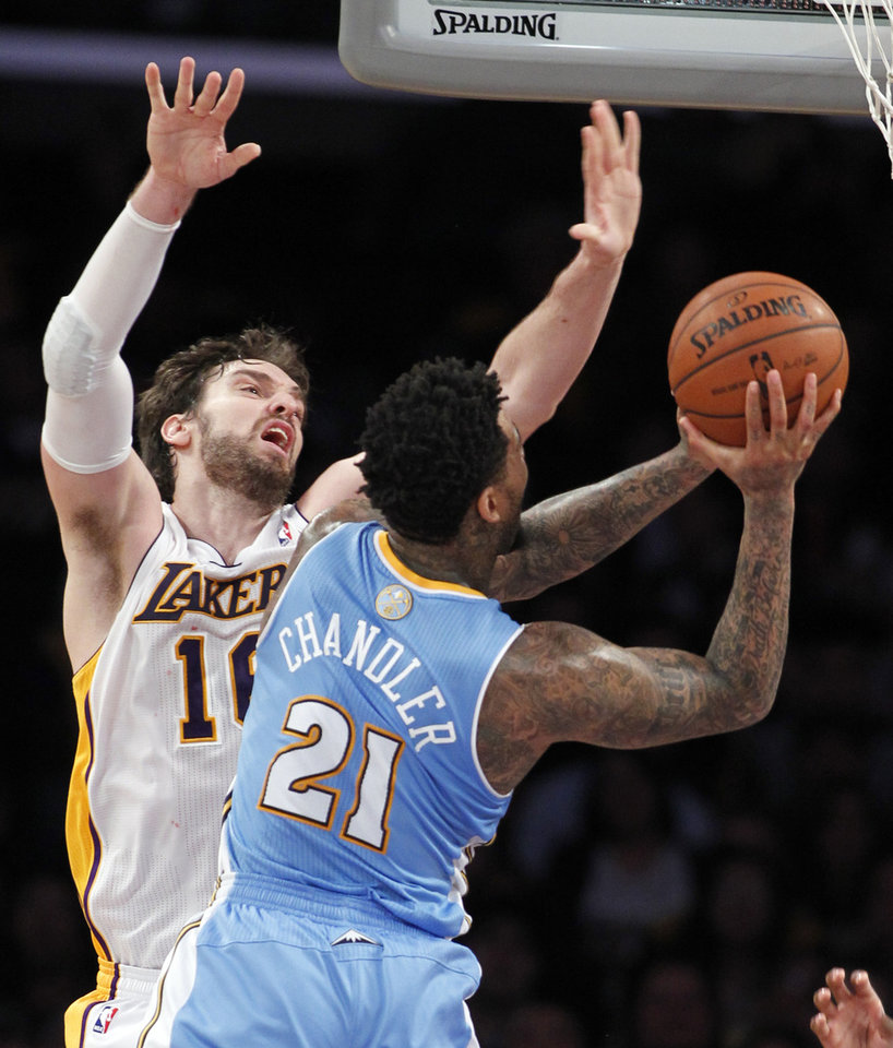 Photo - Los Angeles Lakers center Pau Gasol (16), of Spain, defends as Denver Nuggets forward Wilson Chandler (21) goes up for a shot during the first half of an NBA basketball game, Sunday, Jan. 5, 2014, in Los Angeles. (AP Photo/Alex Gallardo)