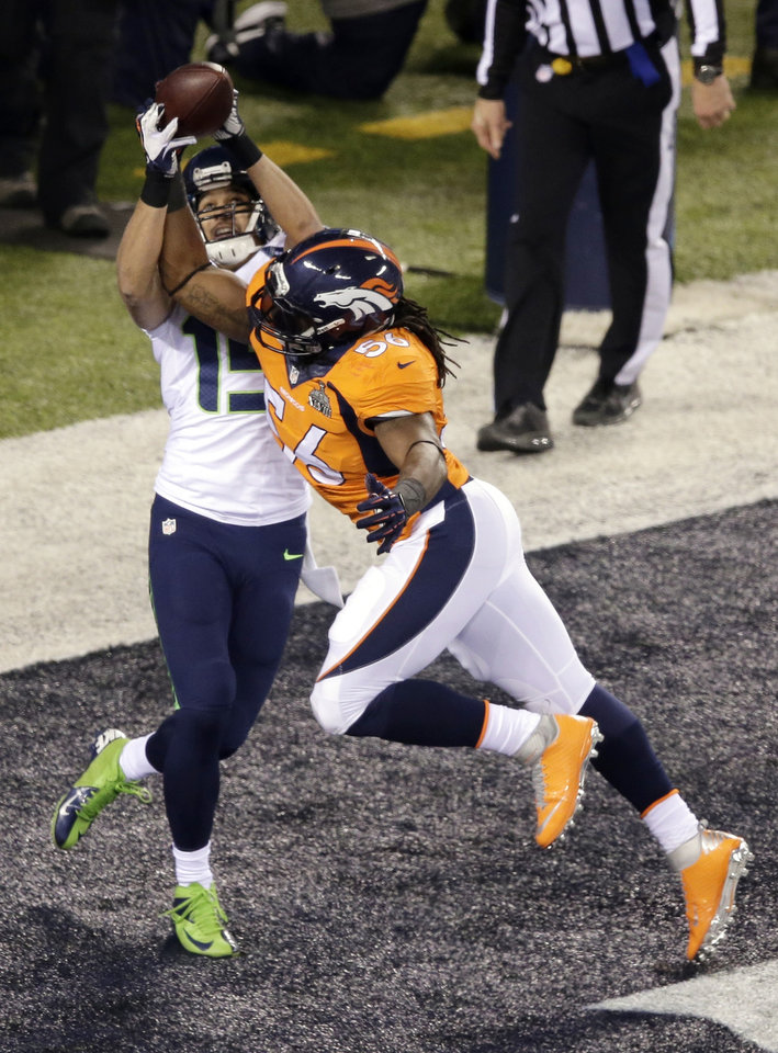 Photo - Denver Broncos' Nate Irving (56) breaks up a pass to Seattle Seahawks' Jermaine Kearse (15) during the first half of the NFL Super Bowl XLVIII football game Sunday, Feb. 2, 2014, in East Rutherford, N.J. (AP Photo/Charlie Riedel)