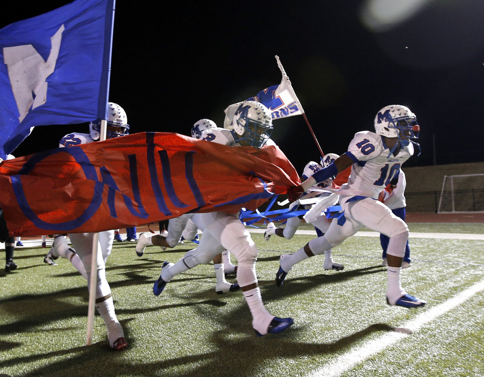 Photo - Millwood's Alfonzo McMillian leads the Falcons onto the field before the Class 2A state football championship game between Davis and Millwood at Moore High School in Moore, Okla.,  Thursday, Dec. 19, 2013. Photo by Sarah Phipps, The Oklahoman
