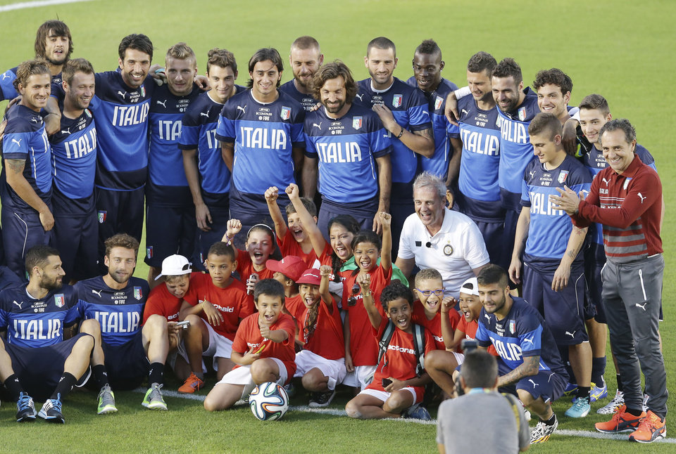 Photo - The Italian national soccer team poses for a photo with visiting children, prior a training session in Natal, Brazil, Saturday, June 21, 2014. Italy proved ineffective in a 1-0 loss to Costa Rica on Friday and now the Azzurri need a win or a draw against Uruguay on Tuesday to reach the second round. (AP Photo/Antonio Calanni)