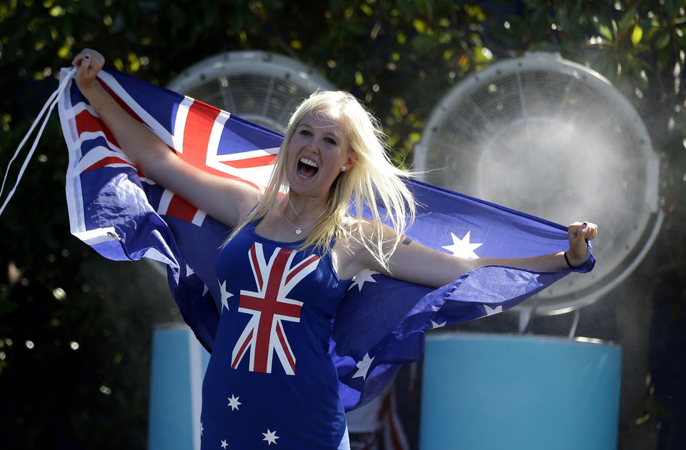 Photo - A spectator cools down in front of a fan spraying cool water while holding the Australian flag during day two at the Australian Open tennis championship in Melbourne, Australia, Tuesday, Jan. 14, 2014. Temperatures hit 40 Celsius (104 Fahrenheit) early afternoon and is expected to rise. (AP Photo/Aijaz Rahi)