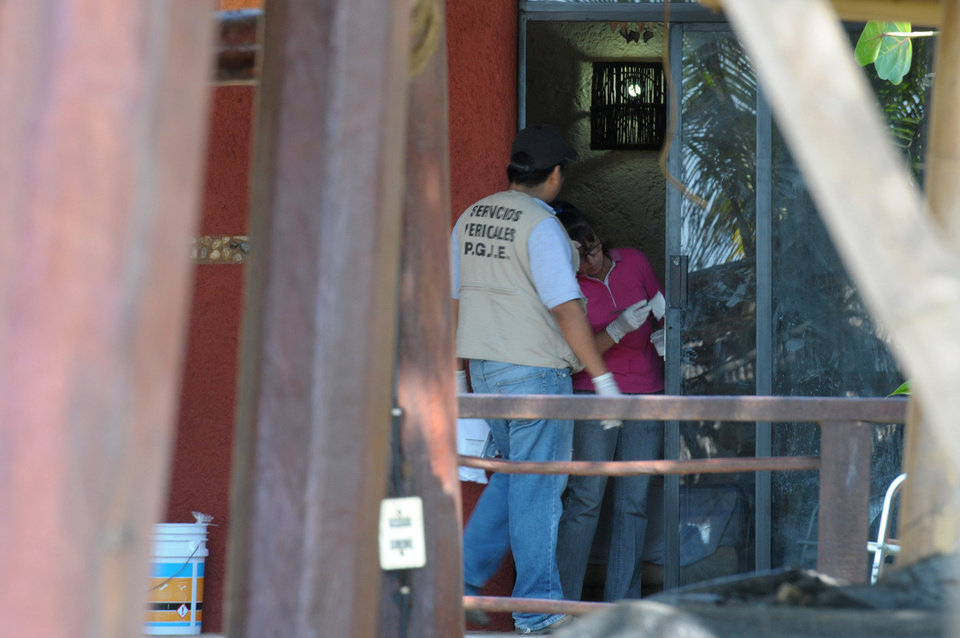 Photo - Police investigators work to obtain fingerprints on a door at the home where masked, armed men broke in, in Acapulco, Mexico, Tuesday Feb. 5, 2013. According to the mayor of Acapulco, five masked men burst into this house that Spanish tourists had rented on the outskirts of Acapulco, in a low-key area near the beach, and held a group of six Spanish men and one Mexican woman at gunpoint, while they raped the six Spanish women before dawn on Monday. (AP Photo/Bernandino Hernandez)