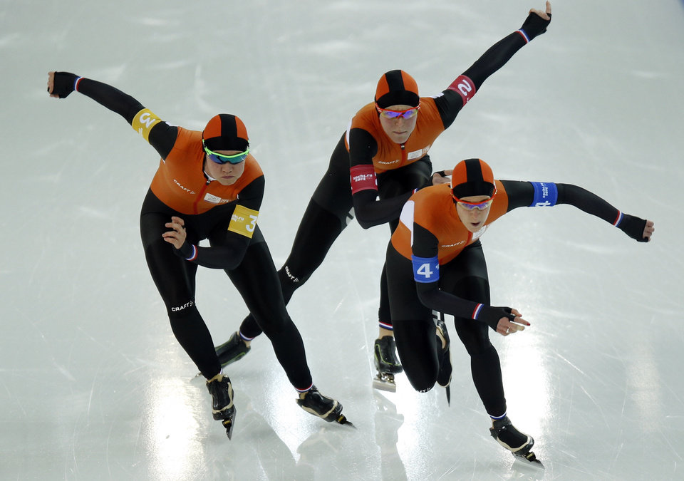 Photo - Speedskaters from the Netherlands, left to right, Lotte van Beek, Jorien ter Mors, and Ireen Wust take the start in the women's speedskating team pursuit quarterfinals at the Adler Arena Skating Center during the 2014 Winter Olympics in Sochi, Russia, Friday, Feb. 21, 2014.  (AP Photo/Pavel Golovkin)
