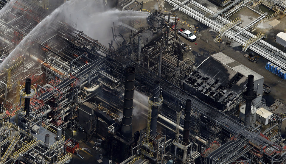Photo - A chemical plant is hosed down after a fire in this aerial photo about twenty miles southeast of Baton Rouge, in Geismer, La., Thursday, June 13, 2013. The plant makes highly flammable gases that are basic building blocks in the petrochemical industry. (AP Photo/Gerald Herbert)