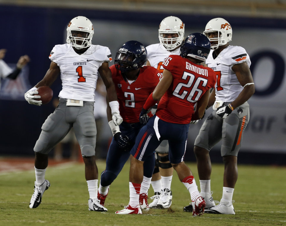 Photo - Oklahoma State's Joseph Randle (1) celebrates in front of Arizona's Marquis Flowers (2) and Jourdon Grandon (26) during the college football game between the University  of Arizona and Oklahoma State University at Arizona Stadium in Tucson, Ariz.,  Saturday, Sept. 8, 2012. Photo by Sarah Phipps, The Oklahoman