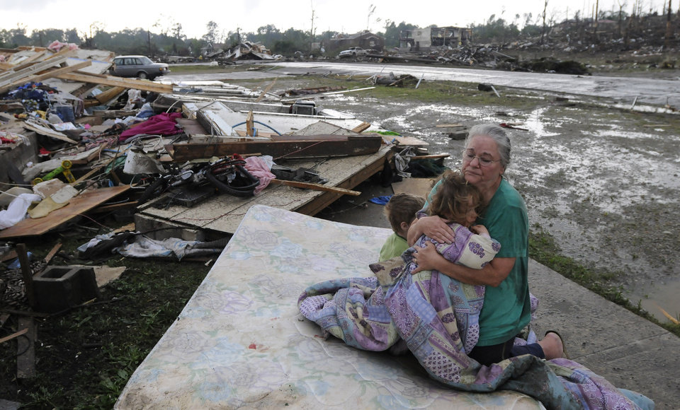 Photo - Faye Hyde, right, sits on a mattress in what was her yard as she comforts her granddaughter Sierra Goldsmith, 2, in Conord Ala. Wednesday, April 27, 2011. Their home was completely destroyed. A wave of tornado-spawning storms strafed the South on Wednesday, splintering buildings across hard-hit Alabama and killing 72 people in four states. At least 58 people died in Alabama alone. (AP Photo/The Birmingham News, Jeff Roberts)