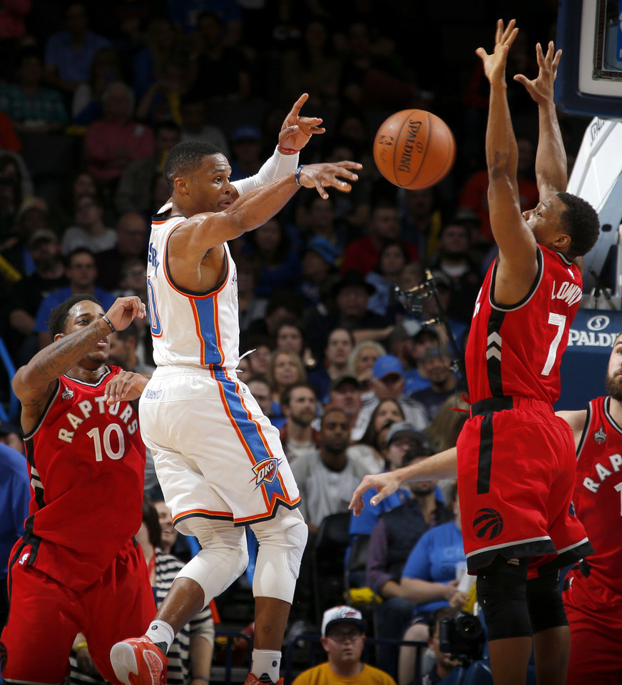 Photo - Oklahoma City's Russell Westbrook (0) passes the ball between Toronto's DeMar DeRozan (10) and Kyle Lowry (7) during an NBA basketball game between the Oklahoma City Thunder and the Toronto Raptors at Chesapeake Energy Arena on Wednesday, Nov. 4, 2015. The Thunder lost 103-98. Photo by Bryan Terry, The Oklahoman
