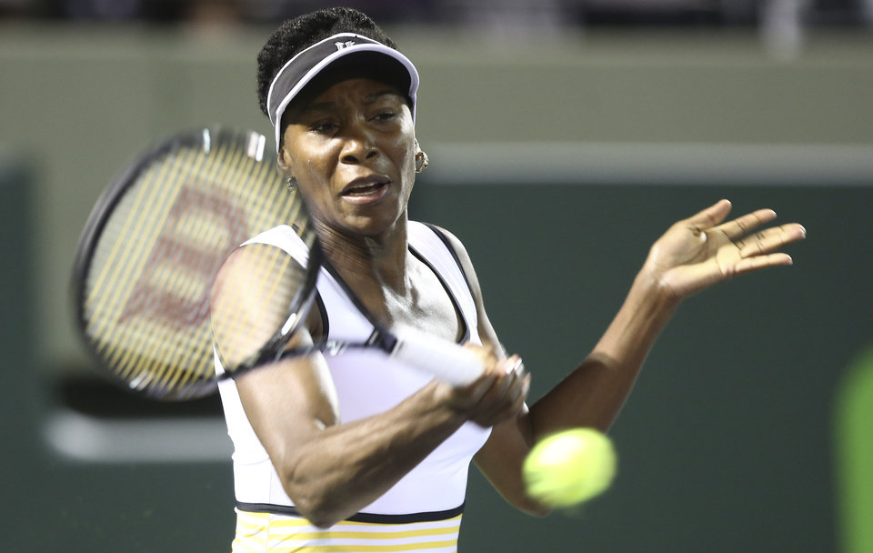 Photo - Venus Williams, of the United States, retuns the ball to Dominika Cibulkova, of Slovakia,during the Sony Open Tennis in Key Biscayne, Fla., Monday, March 24, 2014. (AP Photo/J Pat Carter)