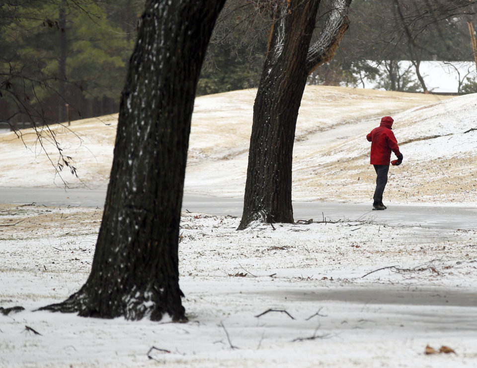 Photo - A person walks through snow in Nichols Hills, Okla., during winter weather, Sunday, Dec. 27, 2015. Photo by Nate Billings, The Oklahoman