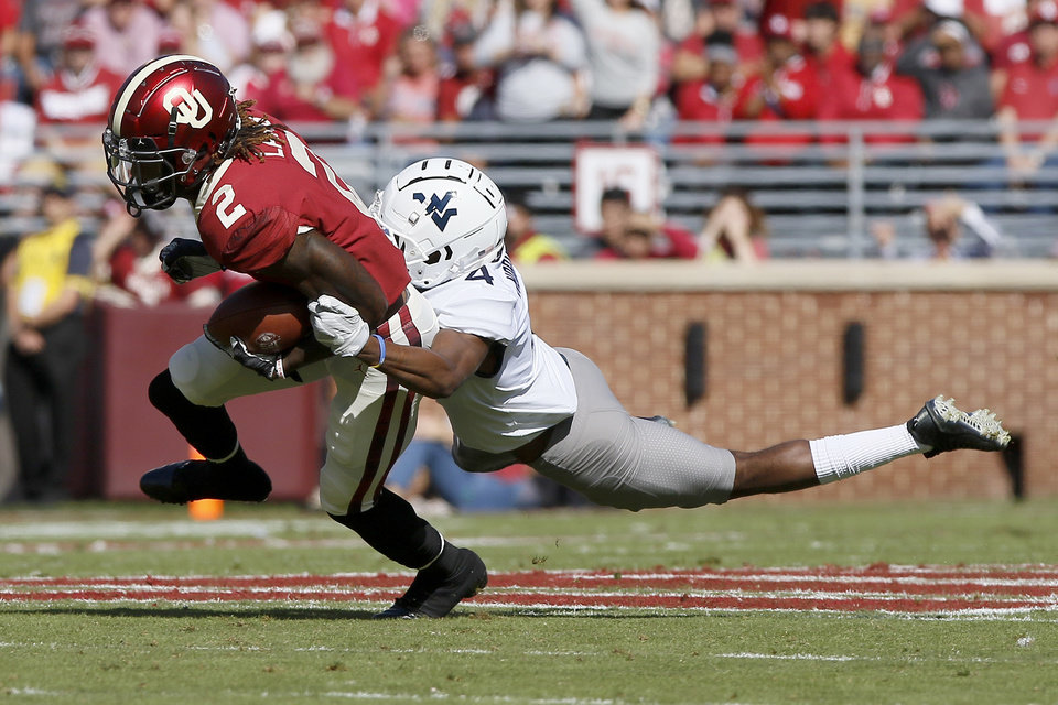 Photo - Oklahoma's CeeDee Lamb (2) is brought down by West Virginia's Josh Norwood (4) during a college football game between the University of Oklahoma Sooners (OU) and the West Virginia Mountaineers at Gaylord Family-Oklahoma Memorial Stadium in Norman, Okla, Saturday, Oct. 19, 2019. Oklahoma won 52-14. [Bryan Terry/The Oklahoman]