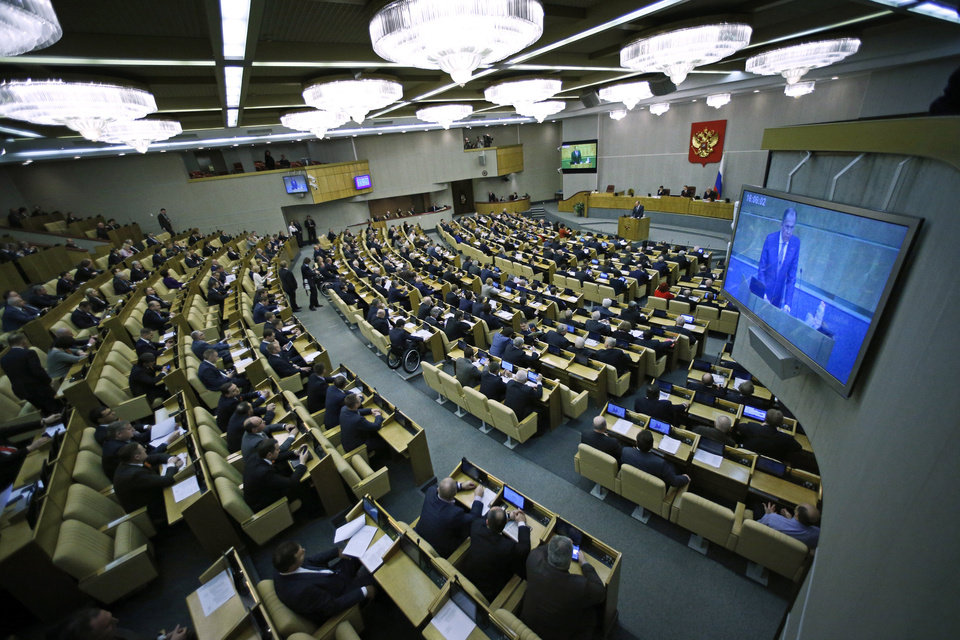 Photo - Members of the State Duma, lower parliament chamber, listens to Russian Foreign Minister Sergey Lavrov, seen on the screen, prior their voting during a plenary session in Moscow, Russia, Thursday, March 20, 2014. The Kremlin-controlled State Duma voted Thursday to allow Crimea to join Russia following a quick discussion in which members of the Kremlin-controlled chamber assailed the Ukrainian authorities. The merger needs to be rubber stamped by the upper house and signed by President Vladimir Putin, mere formalities expected to be completed by the end of the week. (AP Photo/Alexander Zemlianichenko)