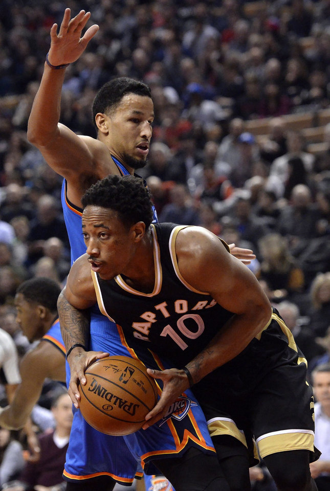 Photo - Toronto Raptors guard DeMar DeRozan (10) moves to the net past Oklahoma City Thunder forward Andre Roberson during the first half of an NBA basketball game Thursday, March 16, 2017, in Toronto. (Nathan Denette/The Canadian Press via AP)