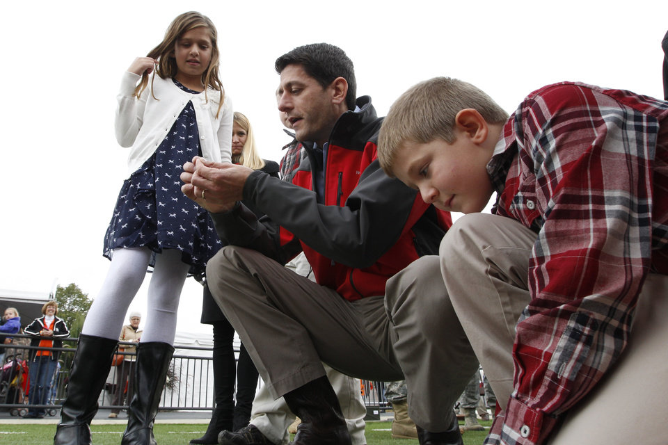 Photo -   Republican vice presidential candidate, Rep. Paul Ryan, R-Wis., talks to his daughter, Liza, and son, Sam, about the stadium astroturf at a Bowling Green State University and Miami University of Ohio football game, Saturday, Oct. 13, 2012 in Bowling Green, Ohio. (AP Photo/Mary Altaffer)