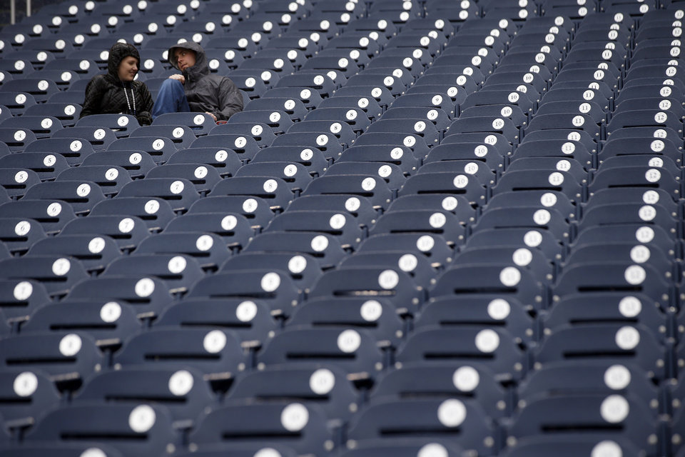 Photo - Alli Engle and Adam Noll, both from Arlington, Va., sit in the rain before an exhibition baseball game between the Washington Nationals and the Detroit Tigers at Nationals Park Saturday, March 29, 2014, in Washington. The game was canceled due to weather. (AP Photo/Alex Brandon)
