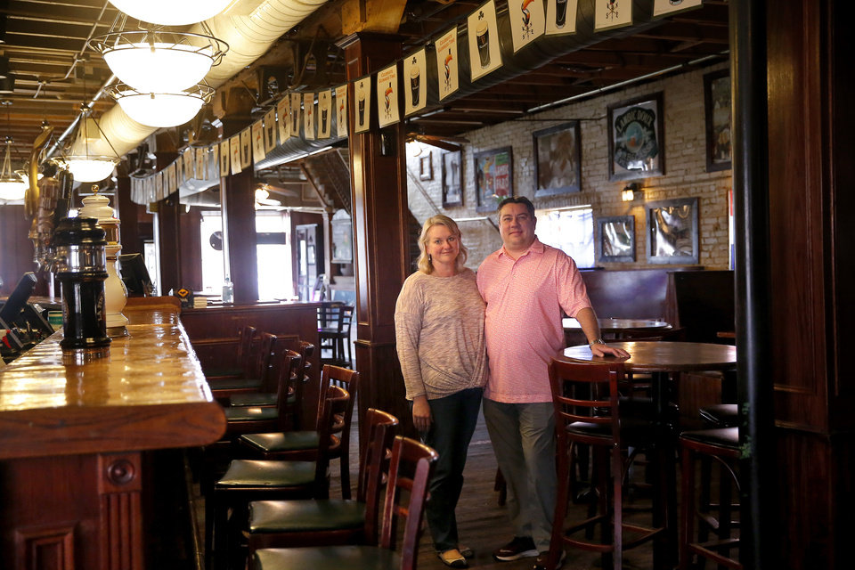 Photo - Jeremy Witzke and Kristy Witzke pose for a photograph in the empty Tapwerks Ale House & Cafe in Bricktown in Oklahoma City, Wednesday, March 18, 2020. [Sarah Phipps/The Oklahoman]