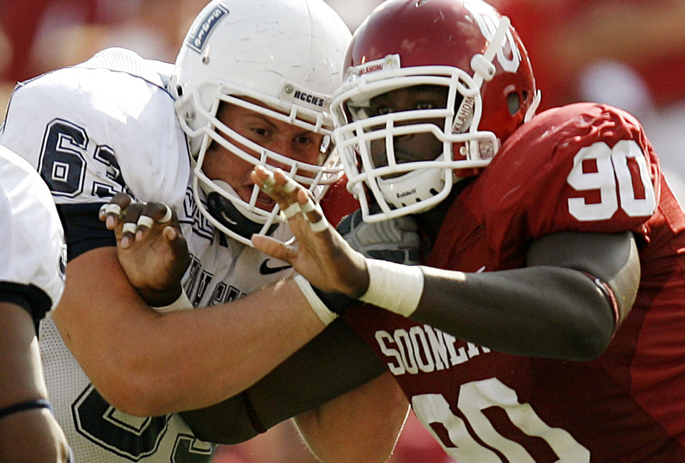 Photo - Oklahoma's Steven Coleman (90) and Utah State's Pace Jorgensen (63) battle at the line of scrimmage in the second half during the University of Oklahoma Sooners (OU) college football game against the Utah State University Aggies (USU) at the Gaylord Family -- Oklahoma Memorial Stadium in Norman, Okla., on Saturday, Sept. 15, 2007.  By NATE BILLINGS, The Oklahoman  ORG XMIT: KOD