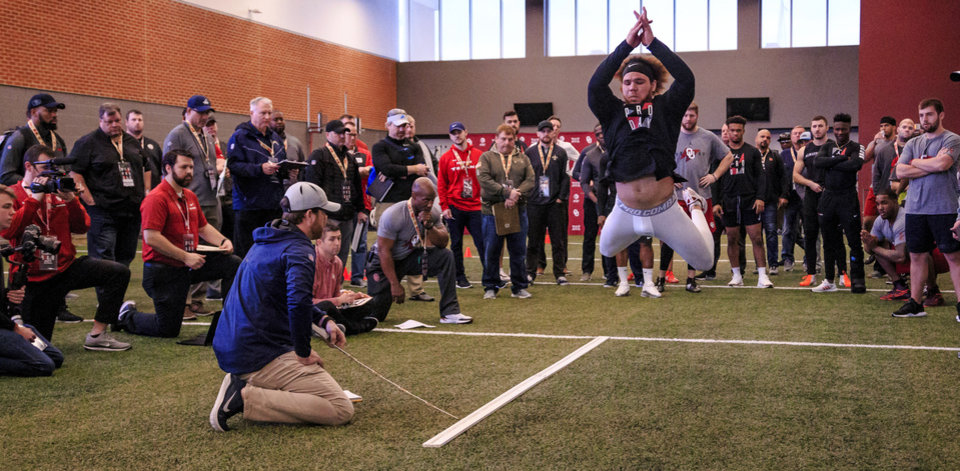 Photo - Curtis Bolton records his broad jump as he works out for NFL scouts during the University of Oklahoma football pro day at the University of Oklahoma in Norman, Okla. on Wednesday, March 13, 2019.   Photo by Chris Landsberger, The Oklahoman