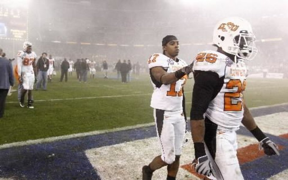 Photo -      OSU's Quinton Moore, right, and Jacob Lacey walk off the field after OSU's loss in the Holiday Bowl college football between Oklahoma State and Oregon at Qualcomm Stadium in San Diego, Tuesday, Dec. 30, 2008. PHOTO BY BRYAN TERRY