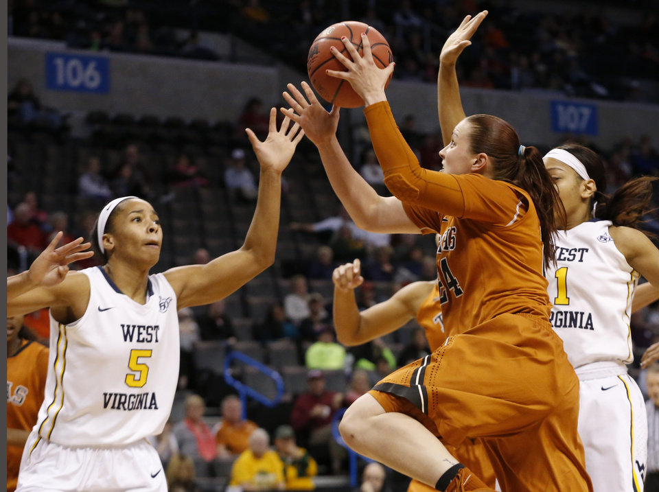 Photo - Texas guard Chassidy Fussell (24) shoots between West Virginia forward Averee Fields (5) and guard Christal Caldwell (1) in the second half of an NCAA college basketball game in the semifinals of the Big 12 Conference women's tournament in Oklahoma City, Sunday, March 9, 2014. West Virginia won 67-60. (AP Photo/Sue Ogrocki)