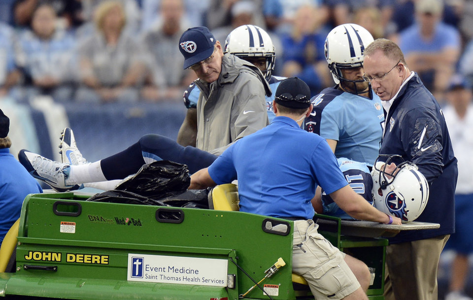 Photo - Tennessee Titans quarterback Jake Locker (10) is taken off the field after being injured in the third quarter of an NFL football game against the New York Jets on Sunday, Sept. 29, 2013, in Nashville, Tenn. (AP Photo/Mark Zaleski)