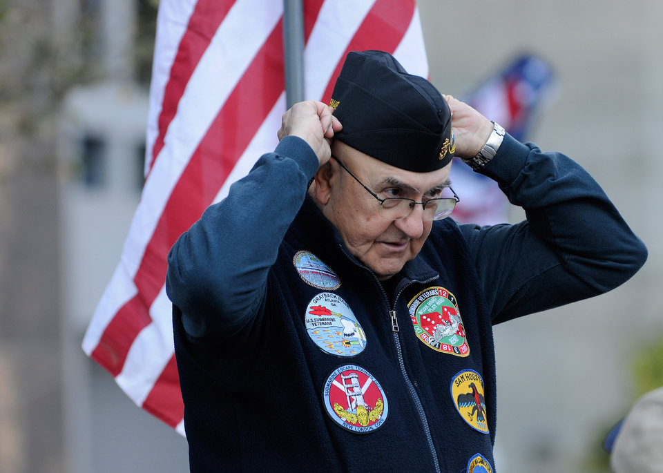 Submarine veteran Lawrence Check, who served on the USS Sam Houston, adjusts his garrison cap during the 31st annual Veterans Day Parade in downtown Atlanta, Saturday, Nov. 10, 2012. (AP Photo/David Tulis)