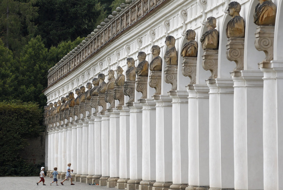 Photo - In this Aug. 7, 2014, photo, children walk in to the 244-meter long colonnade at UNESCO's Flower Garden in city of Kromeriz, in Czech Republic. With its original geometrical layout and high topiary walls, it's a rare example of an early Baroque garden style. And it's now reclaiming the unique features it had when it was completed in 1675, including labyrinths, fountains, sculptures inspired by Greek and Roman mythology, a Dutch bulb garden and citrus trees. (AP Photo/Petr David Josek)