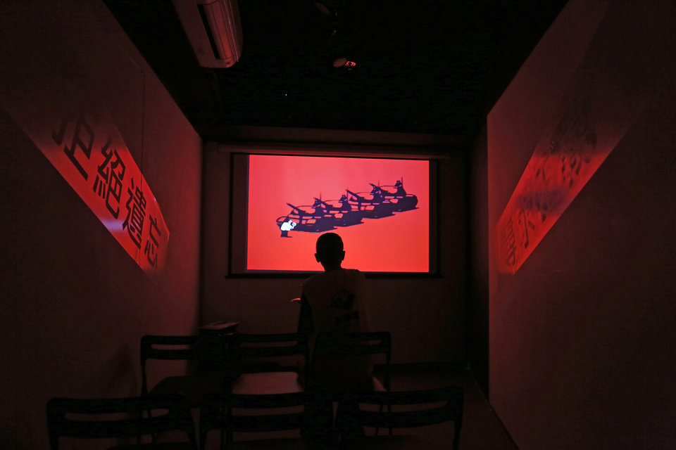 Photo - In this May 28, 2014 photo, a staff member looks at a film at the June 4th Museum in Hong Kong. The 75 square meters (800 square feet) June 4th Museum is the world's only museum chronicling the brutal crackdown on the 1989 Tiananmen protests. The Chinese words on the wall reads