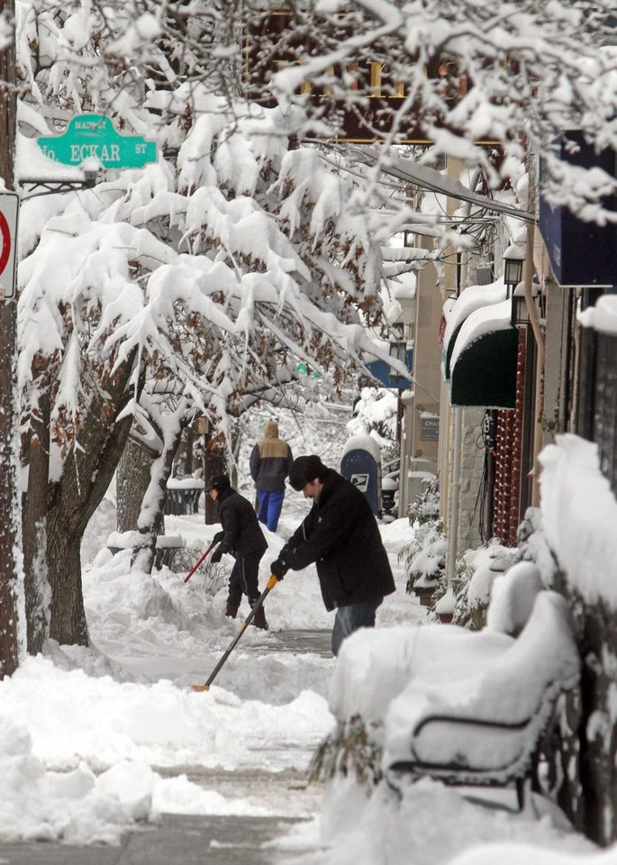 Photo - Shop owners clear the sidewalk in front of their stores on Main St. in Irvington, N.Y., Saturday, Feb. 9, 2013. The year's first major winter storm dumped up to 21 inches on the Lower Hudson Valley.  (AP Photo/The Journal News, Seth Harrison) NYC OUT, NO SALES, ONLINE OUT, TV OUT, NEWSDAY INTERNET OUT; MAGS OUT