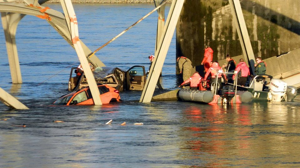 Photo - Rescue workers look for victims after a portion of the Interstate 5 bridge collapsed into the Skagit River in Mount Vernon, Wash., Thursday, May 23, 2013. (AP Photo/Everett Daily Herald, Jon Bauer)